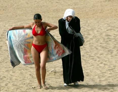 A young woman wearing a bikini walks along the beach with a friend in dressed in traditional clothes at the Palm Beach Club in Algiers July 25, 2003. [It is the summer of 2003 and the scars from a decade of Islamist extremist-linked violence that left between 100,000 and 150,000 people dead in the oil-rich north African country are almost no longer visible.] Temperatures soar above 40 degrees Celsius and people are back on Algeria's beaches escaping the town's heat and having fun